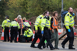 Metropolitan Police officers arrest an Insulate Britain climate activist who had blocked a slip road from the M25 at Junction 25 as part of a campaign intended to push the UK government to make significant legislative change to start lowering emissions on 15th September 2021 in Enfield, United Kingdom. The activists, who wrote to Prime Minister Boris Johnson on 13th August, are demanding that the government immediately promises both to fully fund and ensure the insulation of all social housing in Britain by 2025 and to produce within four months a legally binding national plan to fully fund and ensure the full low-energy and low-carbon whole-house retrofit, with no externalised costs, of all homes in Britain by 2030 as part of a just transition to full decarbonisation of all parts of society and the economy.