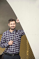 Young man leaning against round arch and smiling, Munich, Bavaria, Germany