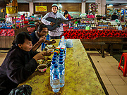 06 AUGUST 2017 - MENGWI, BALI, INDONESIA: A busker performs Indonesian folks songs in the food court of the Bringkit Market in Mengwi, about 30 minutes from Denpasar. Bringkit Market is famous on Bali for its Sunday livestock and poultry market. Hundreds of the small Bali cows are bought and sold there every week. Bali's local markets are open on an every three day rotating schedule because venders travel from town to town. Before modern refrigeration and convenience stores became common place on Bali, markets were thriving community gatherings. Fewer people shop at markets now as more and more consumers go to convenience stores and more families have refrigerators.     PHOTO BY JACK KURTZ
