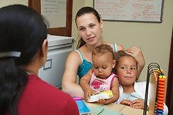 Social worker with young mother and children in office.