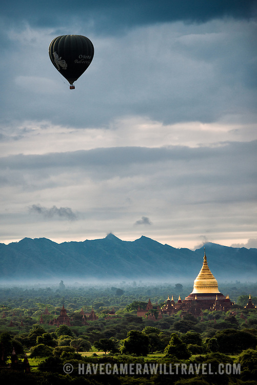 BAGAN, MYANMAR--A hot air balloon carrying tourists flies over the Dhammayazika Pagoda. The Dhammayazika Pagoda (also written as Dhamma-ya-ka Zedi and Dhamma-Yazika) is a Buddhist temple located in the eastern part of the Bagan Archaeological Zone. Completed in 1198, and taking only two years to build, it is estimated that six million bricks were used in its construction. In the 1990s it was completely renovated. It is unusual for its 5-sided design and a highlight is the collection of several hundred tiles telling the jataka stories (about the previous births of Gautama Buddha).