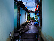 """20 JUNE 2017 - BANGKOK, THAILAND:  The walkway between homes in a community along the Chao Phraya River south of Krung Thon Bridge. This is one of the first parts of the riverbank that is scheduled to be redeveloped. The communities along the river don't know what's going to happen when the redevelopment starts. The Chao Phraya promenade is development project of parks, walkways and recreational areas on the Chao Phraya River between Pin Klao and Phra Nang Klao Bridges. The 14 kilometer long promenade will cost approximately 14 billion Baht (407 million US Dollars). The project involves the forced eviction of more than 200 communities of people who live along the river, a dozen riverfront  temples, several schools, and privately-owned piers on both sides of the Chao Phraya River. Construction is scheduled on the project is scheduled to start in early 2016. There has been very little public input on the planned redevelopment. The Thai government is also cracking down on homes built over the river, such homes are said to be in violation of the """"Navigation in Thai Waters Act."""" Owners face fines and the possibility that their homes will be torn down.              PHOTO BY JACK KURTZ"""