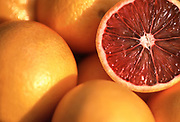 Close up selective focus photograph of a group of Blood Oranges with one cut opened to view the inside