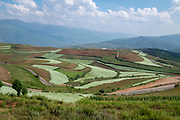 Rural agricultural landscape of rolling hills with fields of various crops. Photographed near Kumming, Yunnan province in southwest China in September