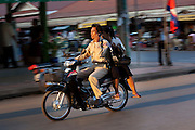 A man drives his motorcycle, talking on his cell phone, in the streets of Siem Reap, Cambodia