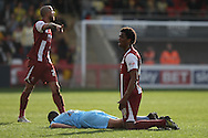 Sido Jombati of Cheltenham protests his innocence over a challenge on Shamir Goodwin of Torquay (on ground). Skybet football league two match, Cheltenham Town v Torquay Utd at the Abbey Business stadium, Whaddon Rd in Cheltenham on Saturday 15th March 2014.<br /> pic by Mark Hawkins, Andrew Orchard sports photography.