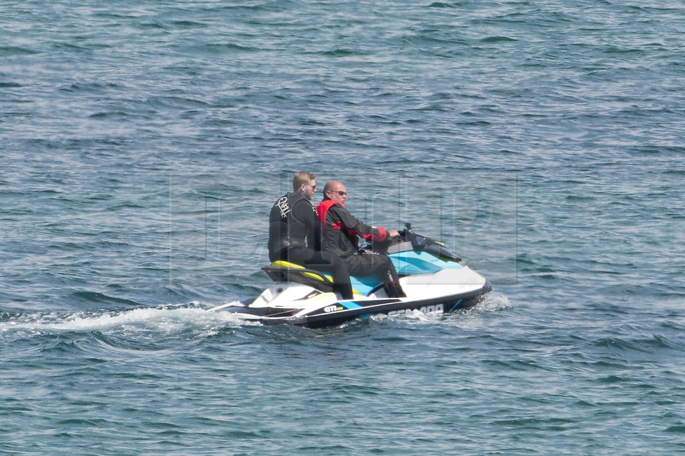 © Licensed to London News Pictures. 22/05/2019. Dorset, UK. People jet ski across the sea in Swanage Bay on a hot sunny day in Dorset, UK. Photo credit: LNP