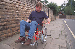 Man with disability; who is manual wheelchair user; looking at soiled hand after wheeling chair through pile of dog mess on pavement,