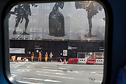 view from the top deck of a London bus, of resting workmen, the  empty traffic lanes in the road and the legs of a construction sheeting covering a large project in Knightsbridge, on 23rd May 2019, in London, England.