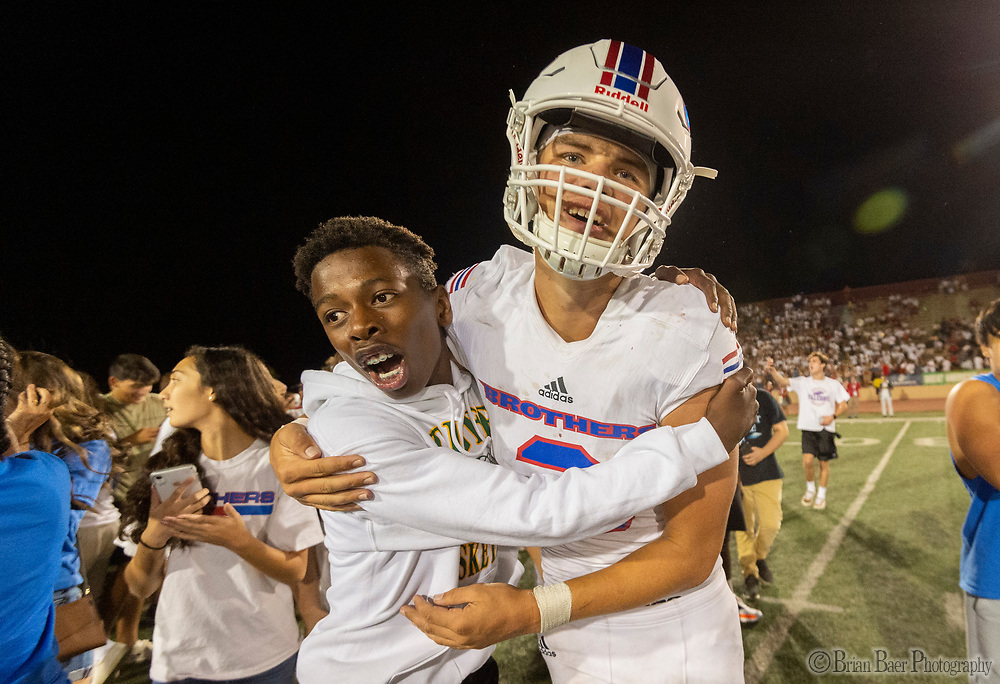 The Christian Brothers Falcons student body hug Christian Brothers Falcons Jacob Stewart (3), after they run onto the field after their 30-27 win over the Jesuit Marauders in the Holy Bowl at Hughes Stadium at Sacramento City College Saturday Sep 14, 2019.