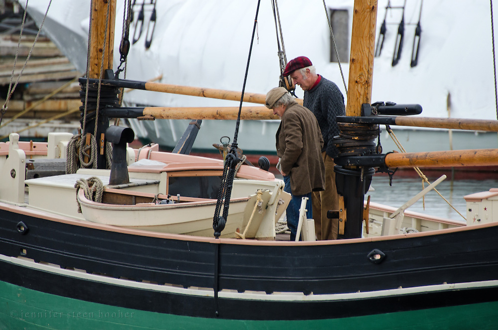Two men examine a wooden boat in the harbor of Camden, Maine (USA).