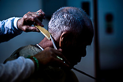 A man gets hair cut at a NGO, which provides free haircut in attempt to encourage employment in Kamagasaki, Japan.