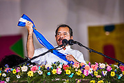 """10 JANUARY 2007 - MANAGUA, NICARAGUA:  DANIEL ORTEGA, President of Nicaragua, holds up the Presidential sash during his inaugural speech in Managua Wednesday night. Ortega, the leader of the Sandanista Front, was sworn in as the President of Nicaragua Wednesday. Ortega and the Sandanistas ruled Nicaragua from their victory of """"Tacho"""" Somoza in 1979 until their defeat by Violetta Chamorro in the 1990 election.  Photo by Jack Kurtz"""