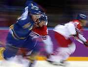 Players from the Czech Republic and Sweden chase the puck in the third period of a men's hockey game at the Winter Olympics in Sochi, Russia, Wednesday, Feb. 12, 2014. Sweden defeated the Czech Republic, 4-2. (Brian Cassella/Chicago Tribune/MCT)
