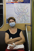 Moscow, Russia, 06/08/2010. .A traveller on the Moscow metro wears a protective mask against the intense smog that has permeated every part of he city in the record high temperatures of the continuing heatwave. Peat and forest fires in the countryside surrounding Moscow have resulted in the Russian capital being blanketed in heavy smog.
