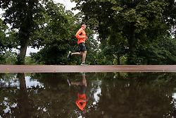 © Licensed to London News Pictures. 07/08/2021. London, UK. A man jogs past a large puddle after heavy rain in Greenwich Park in South East London. A yellow weather warning for thunderstorms is in place for parts of England. Photo credit: George Cracknell Wright/LNP