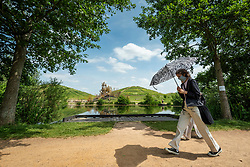 © Licensed to London News Pictures. 15/06/2021. LONDON, UK. A woman shelters from the hot sun under an umbrella at Northala Fields in west London where the temperature is expected to rise to 25C with a forecast warmer 29C tomorrow.  Photo credit: Stephen Chung/LNP