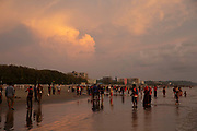 Lots of people on the busy Laboni Beach at sunset in Cox Bazar, Chittagong Division, Bangladesh, Asia. Beachfront buildings of the city can be seen in the background. Sunlight is reflected in the wet sand on the beach.