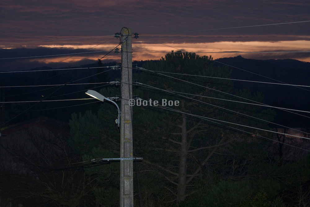 utility pool and electrical wires against a orange sky
