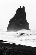 A wave breaks onto Reynisfjara beach at mainland Iceland's southernmost point, with one of the Reynisdrangar sea stacks in the background.