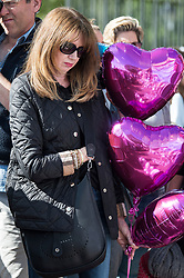 © Licensed to London News Pictures. 31/08/2017. London, UK. A woman places pink balloons at the gates to Kensington Palace in London on the 20th anniversary of the death of Diana, Princess of Wales. Princess Diana was fatally injured in a car crash along with her companion Dodi Fayed, while the couple were being driven through the Pont de l'Alma tunnel in Paris on 31 August 1997. Photo credit: Ben Cawthra/LNP