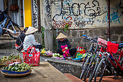 Street photography of Asian lady vendors taking a break from selling their fruit.
