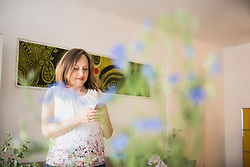 Pregnant woman standing in living room and using on mobile phone, Munich, Bavaria, Germany