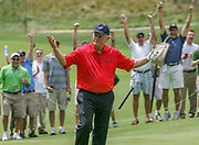 """The crowd reacts as Jack Nicklaus sinks a putt that traveled more than 100 feet, climbing a four foot ridge halfway to the hole.  It wasn't really his putt.  Arnold Palmer failed to get his attempt up the hill.  Palmer's teammate in the scramble match, Johnny Miller, half-jokingly called for a pitching wedge to make the putt.  Nicklaus was standing around the hole when he asked Miller """"would you like me to show you how to putt it?""""  Nicklaus marched down the hill, lined up his putter and sank the shot at the Golf Club at Harbor Shores in Benton Harbor, Michigan. Nicklaus is looking back at Miller to rub it in.  Jack Nicklaus, Johnny Miller, Arnold Palmer and Tom Watson played together for the first time during Champions For Change, which was 18 holes of a scramble skins format with rotating two-man teams to commemorate the opening of the Jack Nicklaus Signature course.  Some holes on the course wind through sand dunes providing views of Lake Michigan."""