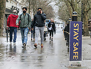 21st February, Cheltenham, England. Shoppers wearing masks walk through the Promenade area of Cheltenham during the third national lockdown.