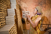 30 JUNE 2006 - PHNOM PENH, CAMBODIA: A brick factory worker stacks unbaked bricks in a kiln in a brick factory in Phnom Penh, Cambodia. The bricks will bake in the kiln, which is fired by wood from an old rubber plantation, for seven days. According the United Nations Food and Agricultural Organization, there are more than 70 brick factories in Phnom Penh and its environs. Environmentalists are concerned that the factories, most of which burn wood in their kilns, contribute to deforestation in Cambodia. They are encouraging factory owners to switch to burning rice husks, as brick kilns in neighboring Vietnam do. The brick factories are kept busy feeding Phnom Penh's nearly insatiable appetite for building materials as the city is in the midst of a building boom brought by on economic development and the need for new office complexes and tourist hotels.   Photo by Jack Kurtz / ZUMA Press