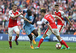 23 April 2017 FA Cup semi-final : Arsenal v Manchester City :<br /> Yaya Toure of City runs into Arsenal defender Laurent Koscielny, who is supported by Aaron Ramsey (left).<br /> Photo: Mark Leech