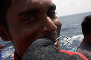A Maldivian fisherman shows a hook and mesh glove used to line catch yellow fin tuna fishing aboard a dhoni boat, Indian Ocean