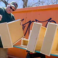 Dan Statile repaints drawer and cabinet faces at Battered Families Services in Gallup Saturday.