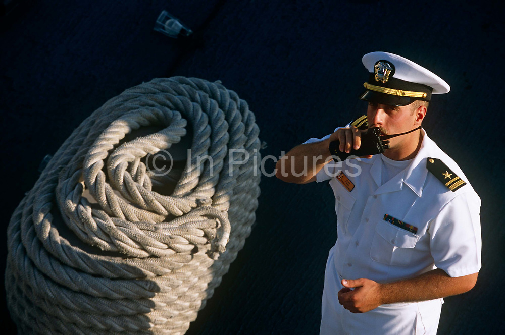 A junior officer speaks into a walkie-talkie to communicate instructions to an unknown member of the ship's company. With a coil of naval line (rope) to his side, the man is dressed in full naval working white uniform and a combination cap. The insignia on his shoulder rates him as a Lieutenant Junior Grade. We are on-board the USS Winston Churchill designated DDG-81, one of the Navy's stealth warships that was on exercise in British waters in 2001. The Churchill is an Arleigh Burke-class guided missile destroyer of the United States Navy. She is the 31st destroyer of a planned 62-ship class. The Churchill is named after the British Prime Minister Sir Winston Churchill. Her home port is in NS Norfolk, Virginia.