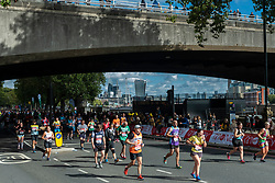 © Licensed to London News Pictures. 03/10/2021. LONDON, UK. Runners on Embankment pass mile 25 in the London Marathon, the first time it has been held since April 2019 due to the Covid-19 pandemic.  Over 36,000 elite athletes, club runners and fun runners are taking part in the mass event, with another 40,000 people taking part virtually.  Photo credit: Stephen Chung/LNP