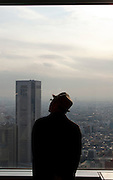 An old man looks-out of the window at the view of Tokyo from the 45th flloor observatory deck at the top of the Tokyo Metropolitan Government building. Shinjuku, Tokyo, Japan.  Wednesday January 7th 2009