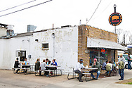 Saw's Soul Kitchen in Birmingham, Alabama's Avondale neighborhood serves up soul food like pork and greens with cheese grits.  Pictured here are the outdoor tables.  Patrons line up at the opening at 11:00am