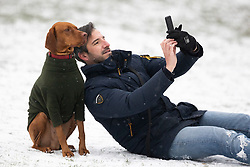 © Licensed to London News Pictures. 08/02/2021. London, UK. A man takes a selfie with his dog in a snowy Greenwich Park in South East London. Snow is expected for large parts of the UK and a yellow weather warning is in place in parts of England as Storm Darcy hits the UK. Photo credit: George Cracknell Wright/LNP