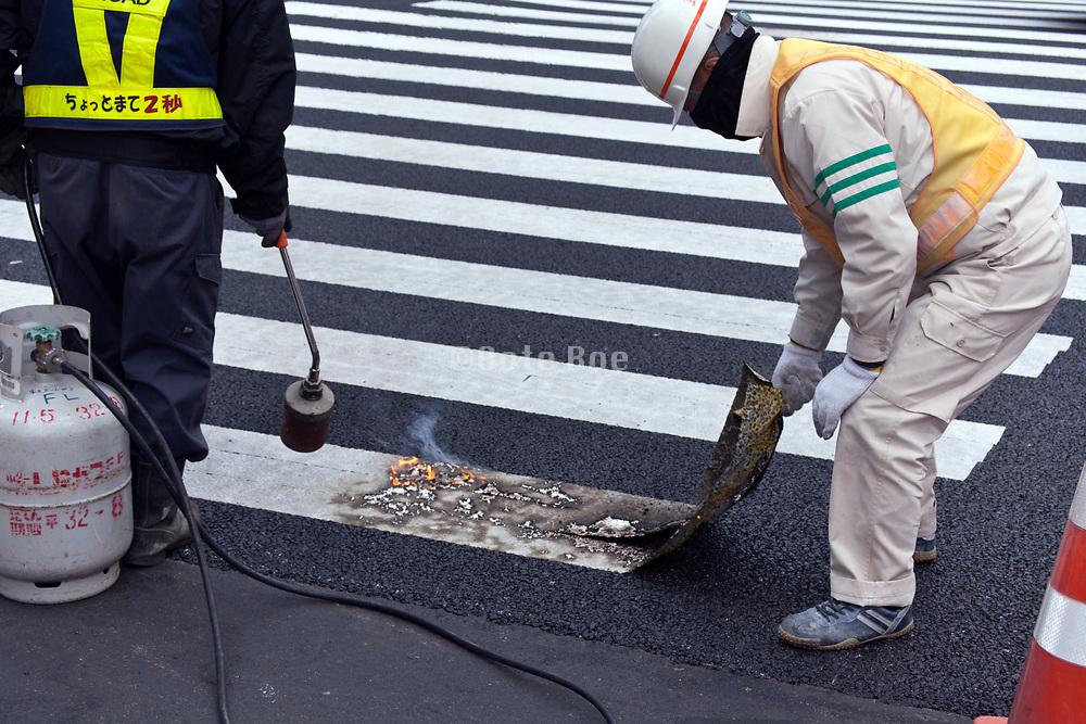 road repair workers burning the pedestrian white stripes of the asphalt Japan