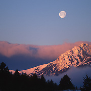 Sunrise over the Bridger Mountains with a full moon. Montana