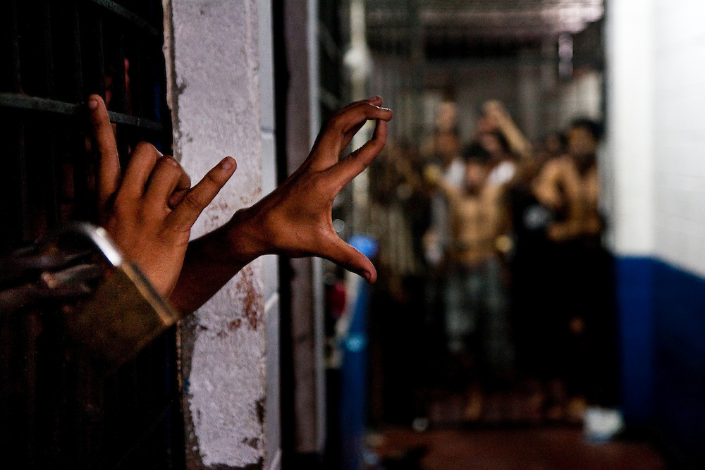"""A member of MS-13 flashes his gang sign out of the MS-13 jail cell in the Ilopango barrio, one of San Salvador's most violent.  The jail is divided into three cells one for civilians, one for 18th street, and one for MS-13. The jails hold detainees for up to four days without food or water in tiny cells with no running water.  In El Salvador """"Mano Duro"""" laws allow the El Salvador police to hold Maras for up to three days with no charges."""