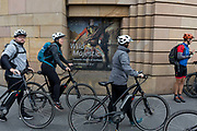 Cycling tourists push their bikes past a poster of Colonel William Gordon of Fyvie by Pompeo Batoni, outside the National Museum of Scotland where the exhibition Wild and Majestic about Scotlands Romantic art movement of the 18th and early 19th century is currently being exhibited, in Edinburgh, on 25th June 2019, in Edinburgh, Scotland.