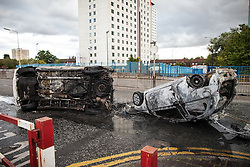 © Licensed to London News Pictures . 09/08/2011 . Salford , UK . Overturned and burned out vehicles at Salford Precinct  as disorder spreads to Manchester during a 4th night of rioting and looting , following a protest against the police shooting of Mark Duggan in Tottenham . Photo credit : Joel Goodman/LNP