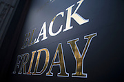 Shoppers on Oxford Street in central London with a sign advertising Black Friday in a shop window on 25th November 2017 in London, England, United Kingdom. This is the busiest shopping district in the capital with Oxford Street being Europes busiest shopping area.