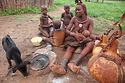 A Himba woman breastfeeds a child while sitting outside her home in Okapembambu village, northwestern Namibia, during the rainy season in March. The Himba diet consists of corn meal porridge and sour cow's milk.