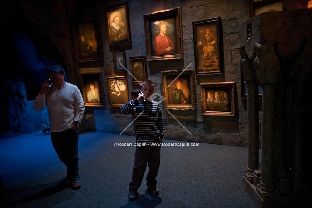 """Hans Iselborn, 9, and his father Daniel Iselborn listen to their audio tour as they enter the """"Harry Potter"""" exhibition at Discovery Times in New York. ..Photo by Robert Caplin."""