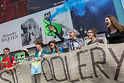 Beneath advertising, young campaigners block Piccadilly Circus  on day 4 of protests by climate change environmental activists with pressure group Extinction Rebellion, on18th April 2019, in London, England.