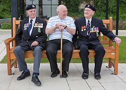 © Licensed to London News Pictures. 29/05/2014. Arnie, Gordon Nash (a civilian who has made the journey with his best friend, Arnie) and David take a rest on a bench as they walk around the Caen Peace Memorial and Gardens. Photo credit : Alison Baskerville/LNP