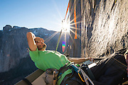 Kevin Jorgeson on the portaledge taking a survey of tiny holds before launching off on an attempt of pitch 14, 5.14d, on the Dawn Wall of El Capitan in Yosemite National  Park. This was on December 22nd, 2014, just weeks before his historic first ascent of the route with partner Tommy Caldwell.