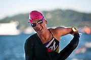 Professional Kelly Williamson begins to rip her wetsuit off as she crosses the finishing line for the swim section of Sunday's Ironman competition..